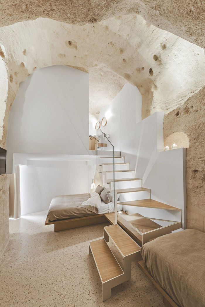 boutique hotel cave interior design with stairs white walls and stones