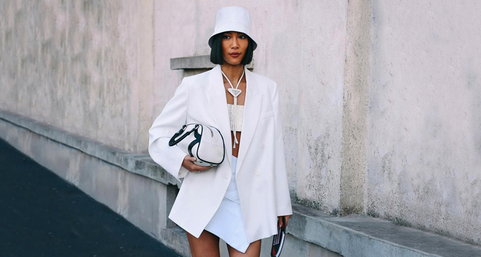 woman wearing all white with a white bucket hat on her head and black short hair walking next to a white wall