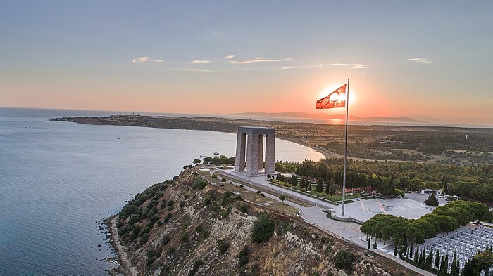 canakkale with the turkish flag and a large stone monument at cape above the sea