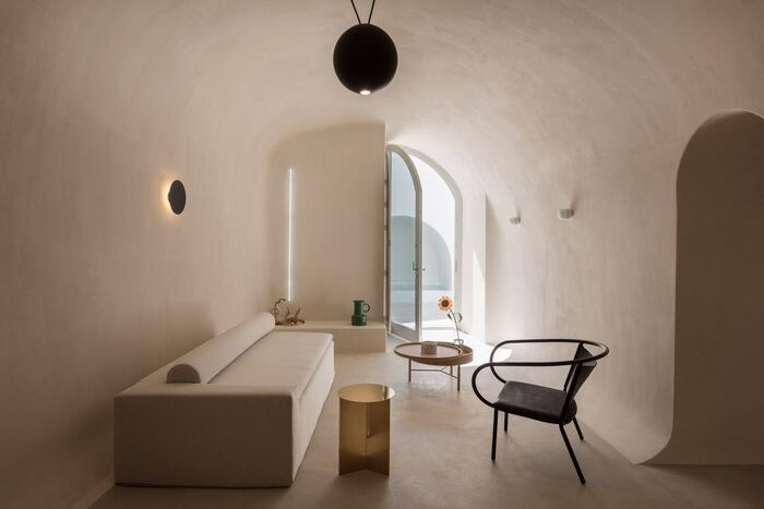 cave house santorini with white sofa and black chair large window open to the outside