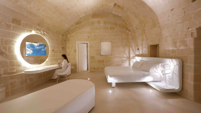 cave room in a hotel white furniture and woman in white gown sitting in front of a mirror