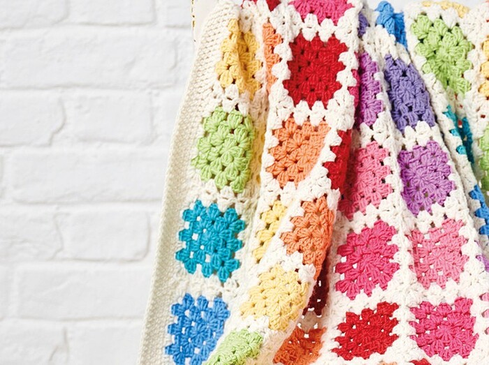 crochet blanket colorful square patterns throw on a white brock wall background