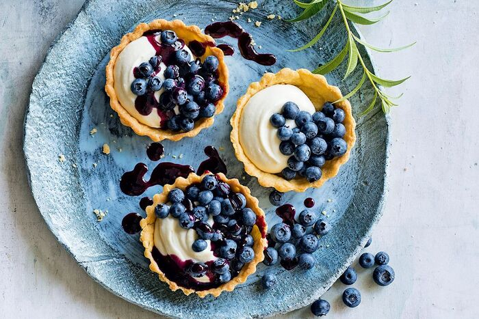 delicious blueberry desserts three baked baskets in a light blue plate with white cream and jam topping