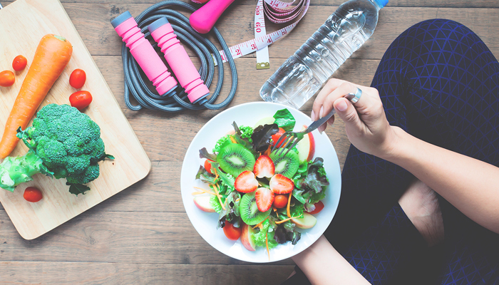 food and workout woman eating from a bowl with veggies and fitness gear around