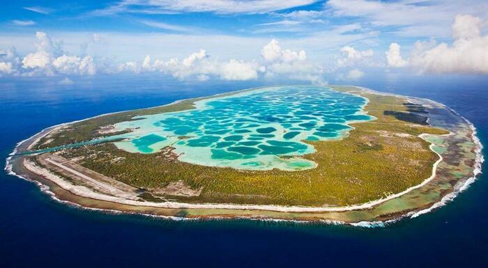 french polynesia beautiful island with bright blue water in the middle and a green ring around it