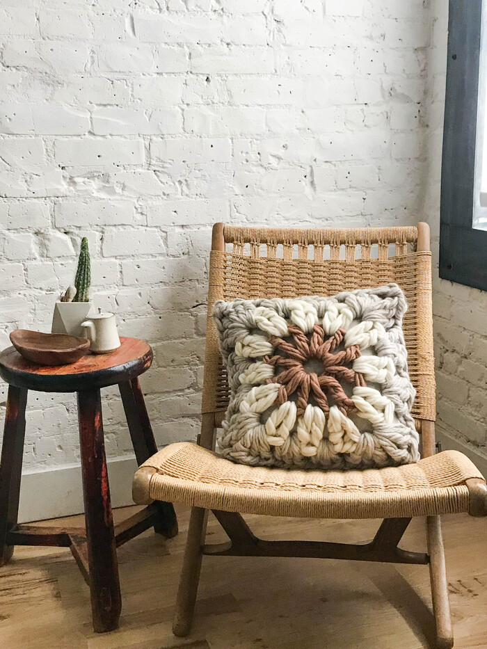granny pillow on a rocking woven chair in a white room with a wooden floor