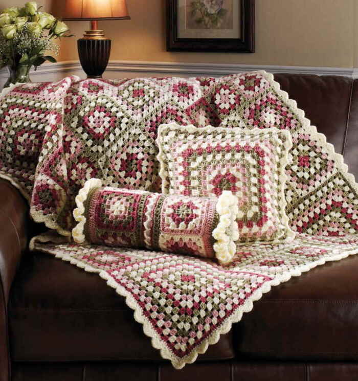 granny squares throw and pillows in colorful pattern on a brown leather sofa