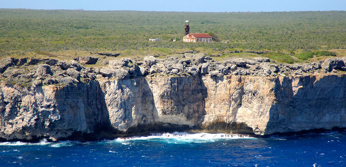 isla de mona with high cliffs and blue waves crashing in them with a lighthouse on the island
