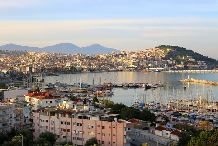 kusadasi tourist photo over the city with a hill on the other side and many boats in the harbour