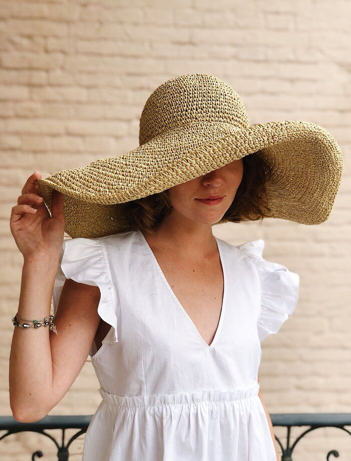 wide brim hat on a woman dressed in a white dress with a brick wall in the background