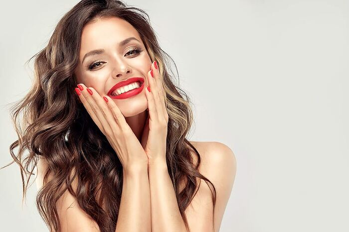 make up and red lipstick woman with a long wavy hair holding her face with two hands smiling with bright red lipstick on