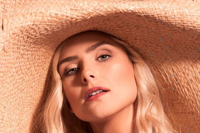 make up tips sunkissed skin blond woman with a large wide brim hat and light eyes looking into the camera