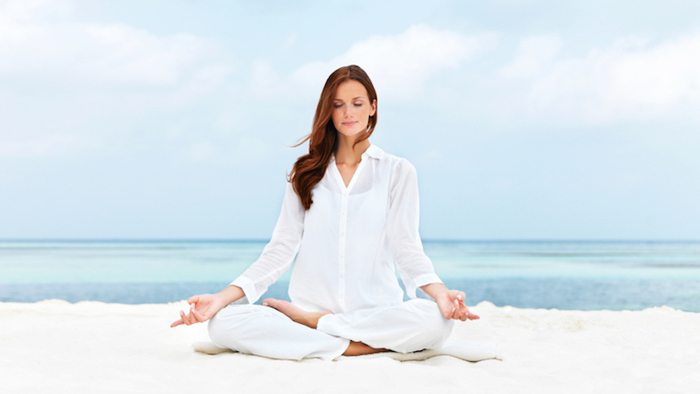 woman sitting on a white sand beach and dressed in white meditating in a lotus pose