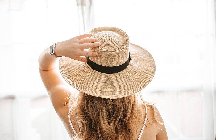 woman with her back to the camera with long hair and a watch holding her hat with wide trip and black accent