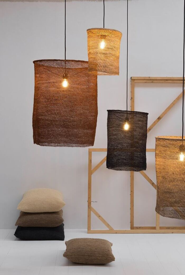natural lamps in different shades of brown hanging from the ceiling with pillows on the floor