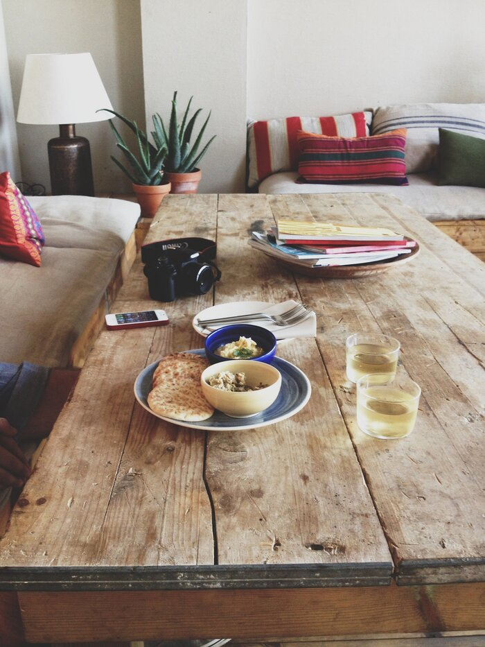 natural wood at home wooden table with food on it camera and living plants in the background