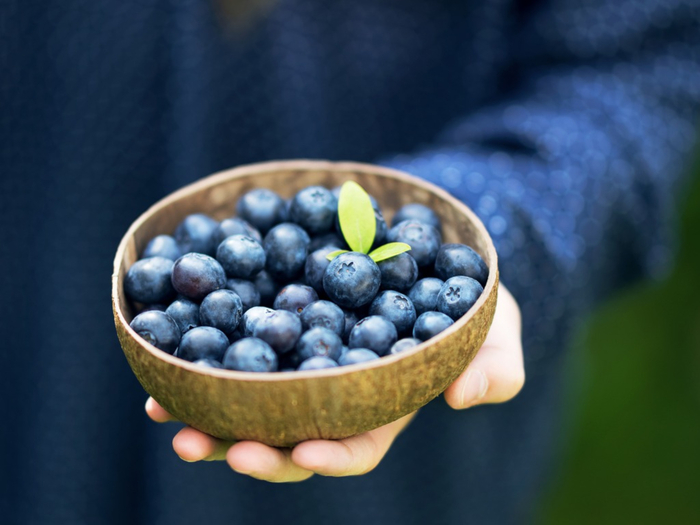 woman dressed in blue holding organic blueberries in a wooden bowl in her hand