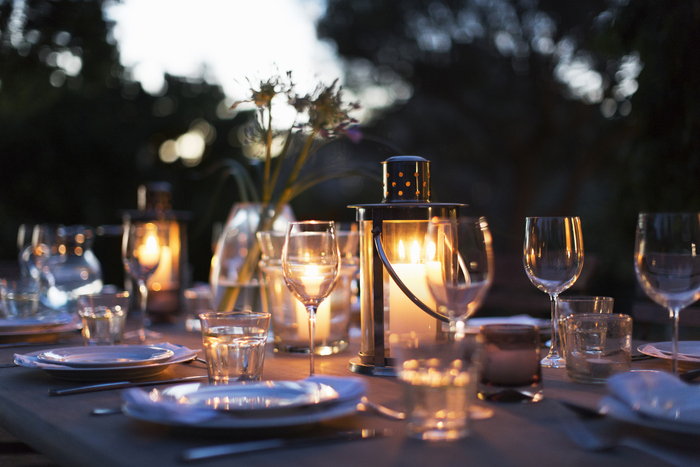 Candles in lanterns on patio dining table with place settings candle lit dinner with wine glasses and plates