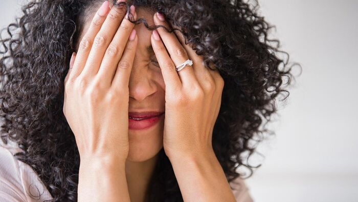 panic attack woman with curly dark hair holding her hands in front of her face
