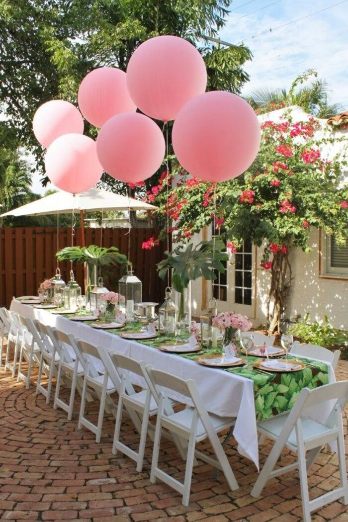 pink party balloons long white table with white chairs in a little yard with flowering plants