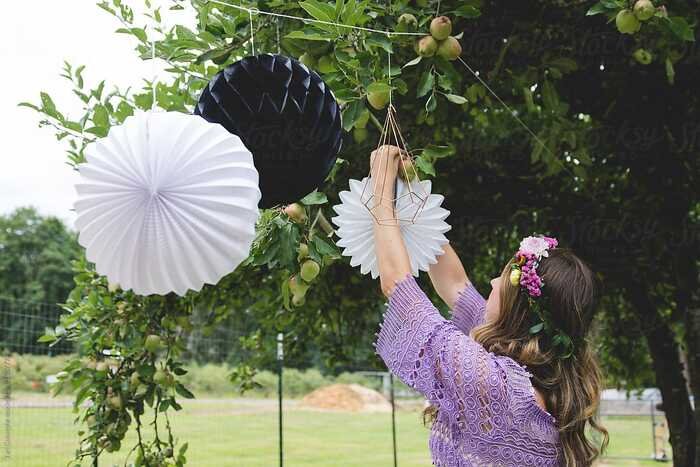 romantic summer party decor woman in purple dress decorating outdoors with large paper rosettes