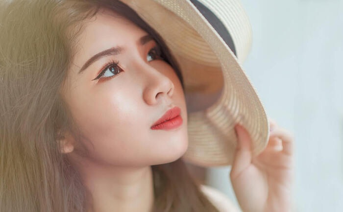 sun and skin asian girl with a sunhat on looking up with light make up