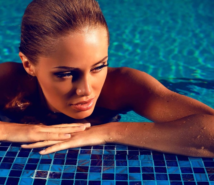 sunkissed woman in a pool close up with her hair back false lashes and natural glowing suntan