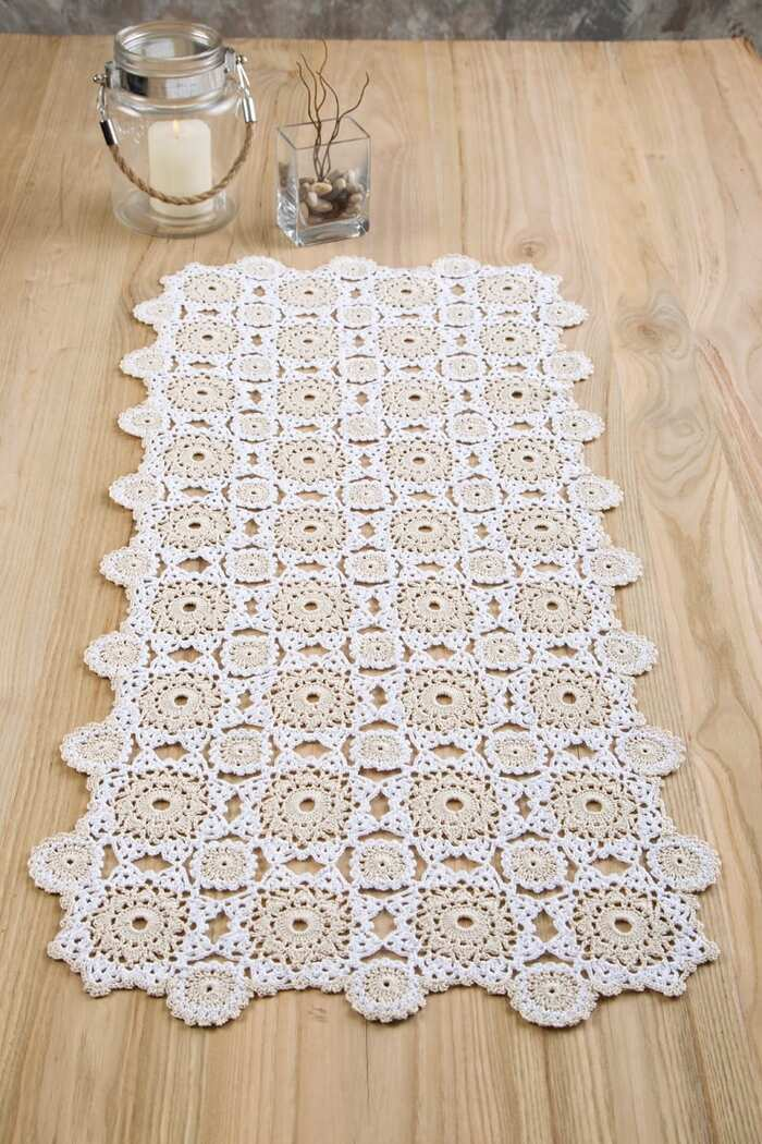 white table runner with granny crochet square patterns on a light wooden table