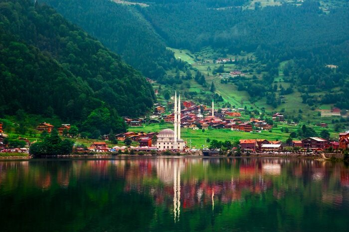 visiting Turkey trabzon a large mosque on a lake surrounded by green forests and houses