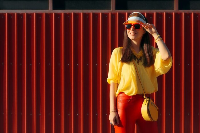 woman wearing visors yellow shirt and red pants with red sunglasses on a red wall