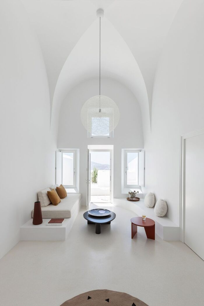 white cave with high ceilings and minimal furniture with colorful accent tables