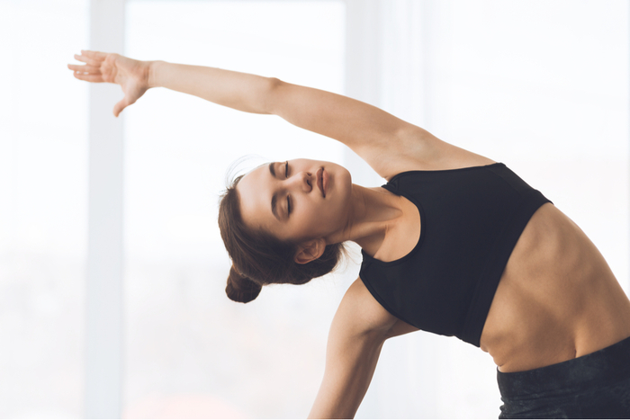 woman dressed in black doing yoga posture with her hair up in a bun