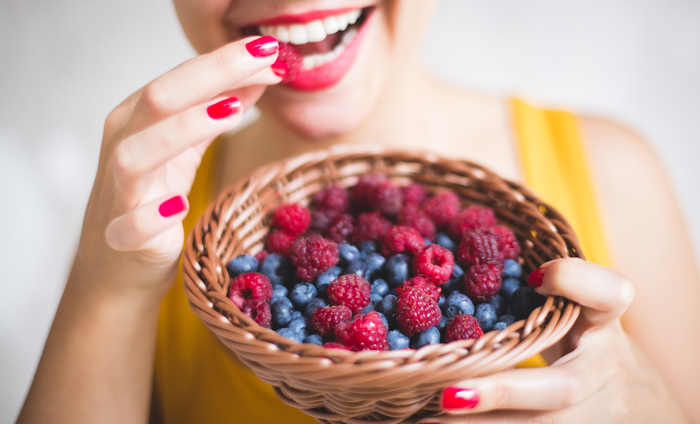 woman in yellow dress with red nail polish and red lipstick eating different berries from a basket