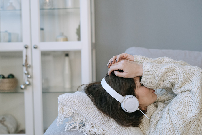 woman in a chunky white sweater listening to music relaxing on a couch and holding her head with her hands