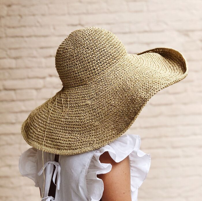 woman wearing a wide brim summer hat with a brick wall in the background