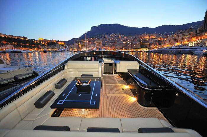 yachts of Monaco luxury yacht deck with wood and leather furniture party table and evening lights in the background