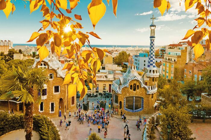 barcelona gaudi park tourist sight and yellow leaves on branches in the forefront