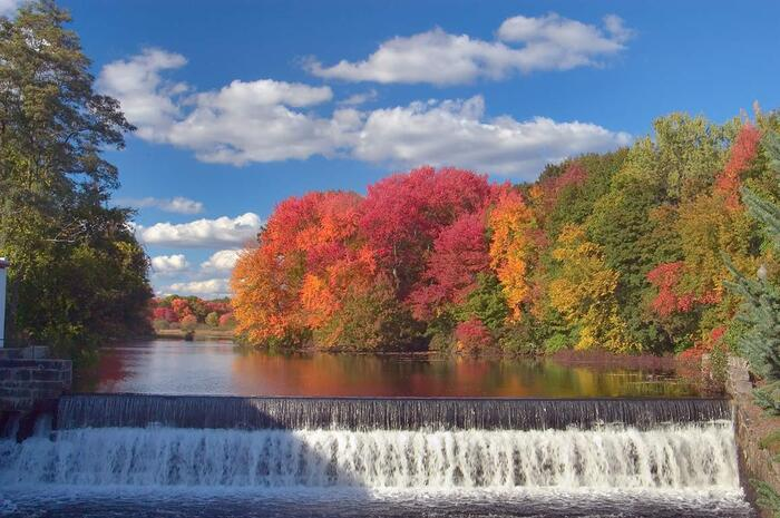 blackstone river small waterfall with colorful trees in the background