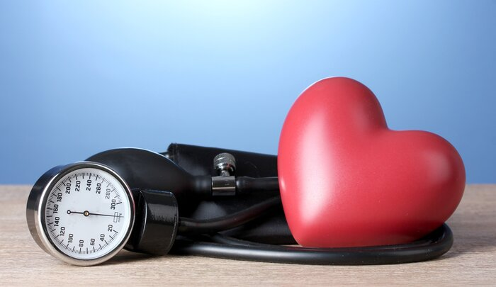blood pressure measuring device on a wooden surface and a light blue background and a large red heart