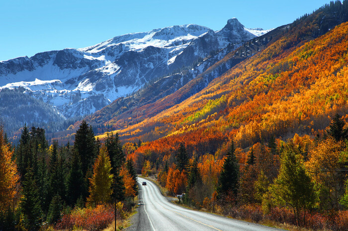 colorado road with a car on it and mountains with snowy peaks in the background fall slopes with colorful foliage