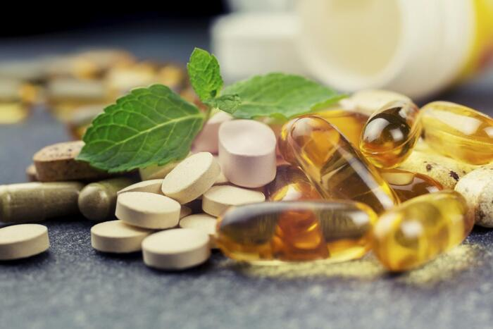 essential supplements pile of pills and capsules and a green mint on top