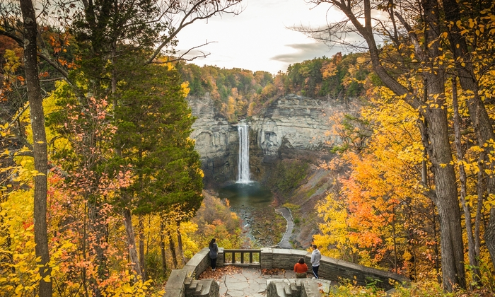 beautiful nature in fall people standing on a stone terrace overlooking at a waterfall surrounded by rocks and colorful trees