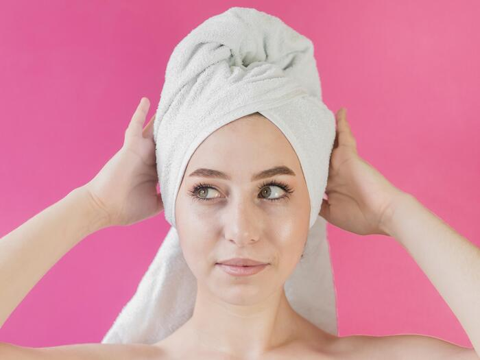 woman with a white towel on her hair face close up on a bright pink background holding her head with hands