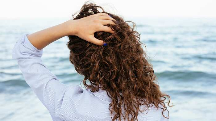 hair in the sun woman looking at the sea and touching her hair back shot