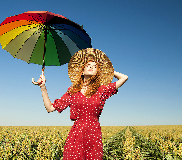 red-haired woman in a dotted red dress in a field with a sun hat and a large colorful umbrella looking at the soon with her eyes closed
