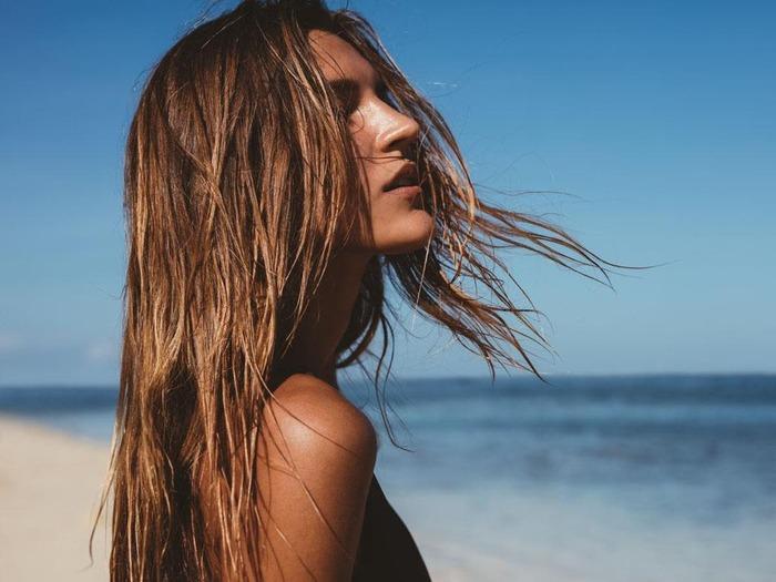 woman on the beach with her hair down enjoying the sun