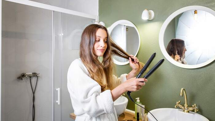 woman in a white bathrobe in front of two mirror in the bathroom styling her hair with a hairpress
