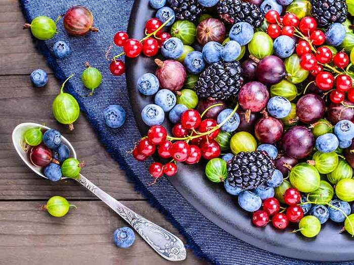 healthiest berries a large bowl with different berries on a table with blue table cloth and a tea spoon