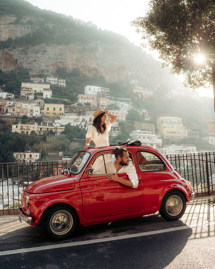 italian trip a couple in a small red mini car looking behind driving down the Amalfi coast