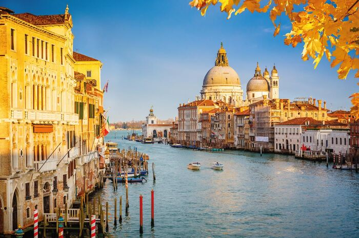 italy fall venice sunlit canal with duomo in the background and yellow leaves in the forefront